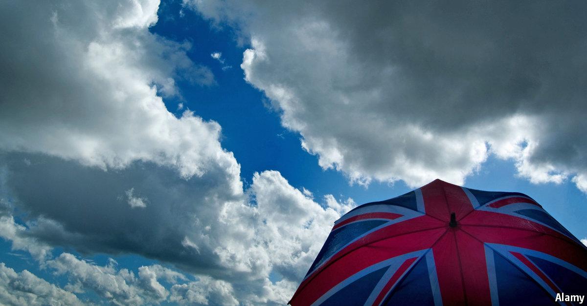 C2F7B0 Brexit,Union jack umbrella against a cloudy, stormy sky. British economic / weather concept.